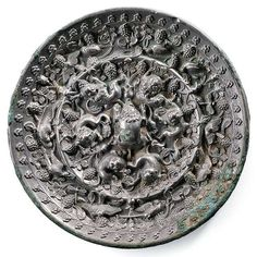 A Tang Dynasty 'lion and grapevine' mirror, circa (618-907 AD).