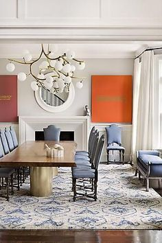 Dining room with a magnificent light fixture of balls and branches and bold orange art.
