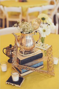 Beautiful vintage centerpieces: each table is different, and has minimal flowers. More like a collection of vintage objects. Love the tea pot, books and frame here, plus the small beaded pearl accent. Vintage Wedding Centerpieces, Wedding Table, Wedding Decorations, Shower Centerpieces, Book Centerpieces, Centrepiece Ideas, Tipi Wedding, Party Wedding, Garden Wedding