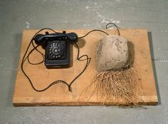 """JOSEPH BEUYS Erdtelephon (Earth Telephone) 1968 Telephone, cords, clump of earth with grass on wooden board 7 7/8 x 29 7/8 x 19 1/4 inches 20 x 75.9 x 48.9 cm Signed and dated in pencil on wooden board, verso: """"Joseph Beuys 68"""""""