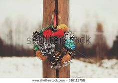 Handmade small christmas wreath hanging outdoors on winter nature background