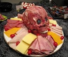Zombie meat covered skull with ham and roast beef surrounded by deli foods! …
