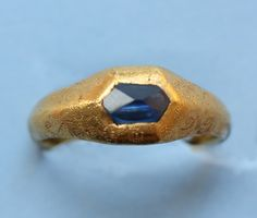 An important high carat gold medieval ring set with a natural irregular octahedron cut sapphire, decorated with fine engravings and inscribed on the inside of the shank with the text 'Loyal Desir' which means legal or loyal desire which indicates the ring is a love token; for marriage or just a token of affection, early 15th century.