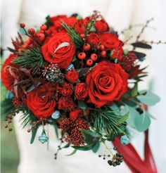 Textured bouquets of cedar foliage, seeded eucalyptus, red roses, red spray…