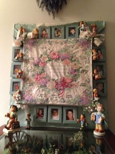 cross stitch kit completed several years ago has name & birth date of each grandchild and a picture; flowers are from my corsage from son's wedding; the Hummel  Merry Wonderer, Christmas gift 2014, the look-a-like Hummel, boy holding shoes, a gift from my son over 20 yrs ago; small Hummels pinned around frame are Christmas ornaments.