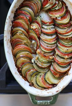 There is something so incredibly satisfying about a vegetable tian. Finely sliced rounds of potatoes, tomatoes and zucchini are arranged like colorful, fallen dominos and roasted to perfection. But not only is this dish beautifully rustic, the flavors are vibrant and savory. Honestly, I've