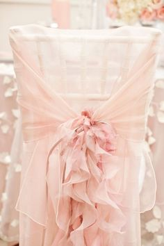 Chiffon chair cover in soft pink with ruffles. I love the matching tablecloth with white flower petal garlands trailing down. So romantic. Do this for wedding or to vanity or boudoir chair or spring or Easter brunch party.