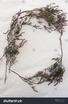 Purple autumn heather (erica) frame on ecru piece raw cotton fabric.
