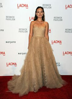Olivia Wilde - strapless champagne colored gown featured a pleated bodice and a full ruffled skirt. (Brand: Monique Lhuillier)