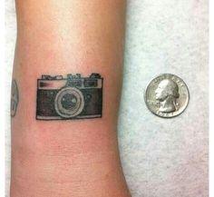Camera tattoo. I'd want it on my wrist/lower arm