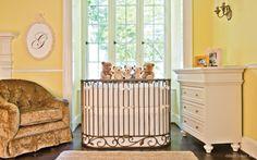 Ivory crib bedding in a Bratt Decor oval crib with yellow walls