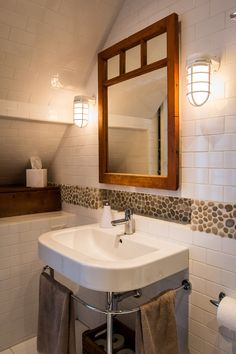 The vanity mirror is a salvaged window with a mirror behind and attached to a box. Digging the pebble tile with subway tile, light fixtures and the simplicity of the sink.