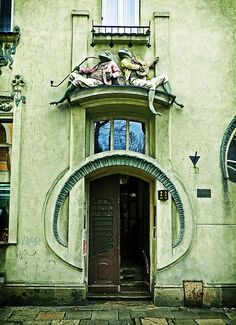 The Frog House (Polish: kamienica Pod Żabami) is an example of art nouveau architecture in the city of Bielsko-Biała, in southern Poland's Silesia Province. It features two frogs seated over the entrance, one smoking a pipe and the other playing a mandolin, while beetles roam freely over the walls. The Frog House stands on Bielsko-Biała's Polish Army Square (plac Wojska Polskiego). // photo by Phillip W, 2009.  Article from http://en.wikipedia.org/wiki/Frog_House