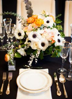 An anemone centerpiece with orange ranunculuses | Brides.com
