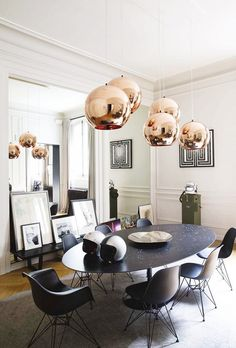 Bold dining room with rose gold pendant lights, and Eames chairs