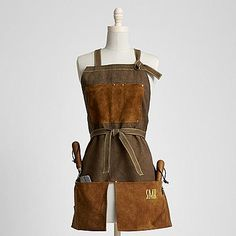 Who knew you could look so refined while pruning, digging and weeding? This smock is fashioned after traditional English garden aprons with strings that tie at the waist and a split at the front trimmed in authentic cow suede. With its deep pockets, antiqued brass finish hardware and contrast stitching, she'll be ready to take on the dirty work in style. Exclusively from RedEnvelope.