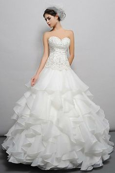 Gorgeous Luster Satin and Organza gown with a sweetheart neckline and heavily beaded and embroidered bodice, sits above a fully ruffled chapel length skirt. Available in White or Ivory.
