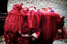 """The Mistresses of Joe Cain, a Mardi Gras mystic society representing the many lovers of  Cain, drink to console themselves during the """"procession"""" parade on Joe Cain Day, Mobile, Alabama, United States, 2012, photograph by Wesley Lowe. In addition to his many wives, the Joe Cain Day parade is today also flanked by his many mistresses. Both groups, flagellating in the streets as they caterwaul over who was Cain's favorite, vie to be the most-loved, sometimes leading to entertaining fights."""