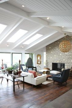 stone fireplace, white walls, ceiling beams