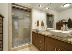 Master bathroom // Dual, square, vessel sinks, large shower with pebble tile work, oversized mirror
