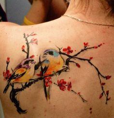 Beautiful cherry blossom tattoo on the shoulders with two birds. The birds give the cherry blossoms and even romantic vibe as they stare into each other while silently passing time on the tree branch.