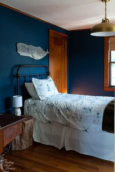 Deep navy walls, brass pendant and a hand carved whale for a boy's bedroom | Finding Silver Pennies #coastal #boysbedroominspiration #homedecor #coastalbedroom Coastal Inspired Art, Coastal Style, One Bedroom, Bedroom Decor, Bedroom Ideas, Pine Chests, Navy Walls, Woven Shades, Library Table