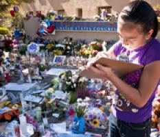 """A young girl writes a note to add to the spontaneous tribute memorial outside Congresswoman Gabrielle Giffords' office. The memorial grew in response to the shooting of Giffords and 18 others at her """"Congress on Your Corner"""" constituent event on January 8, 2011 in Tucson, Arizona. Photo by Jack Kurtz/ZUMAPRESS.com."""
