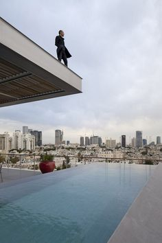 A rooftop swimming pool runs along the edge of this renovated penthouse in Tel Aviv.