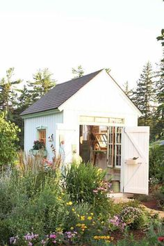 What a peaceful garden shed. The salvaged windows and green trim add a little vintage flair to this cozy potting shed. #pottingshed
