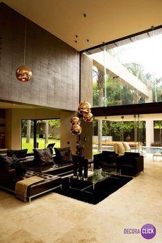Hoje é dia de SALA DE ESTAR! O sofá de couro preto e os pendentes dourados contrastam perfeitamente e dão uma elegância para a sala de estar. A janela de vidro cria uma integração com a área externa e a sensação de um ambiente maior com a luz natural. Projeto: Nico van der Meulen