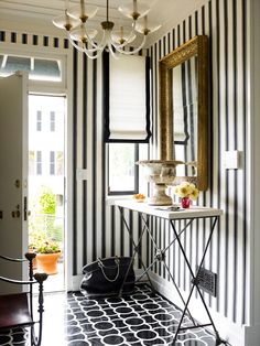 Make an Entrance. Black and white striped wallpaper and tape-trimmed roman shade. Interior Designer: Hilary Thomas.