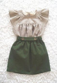 A cute but also a little tough little skirt in a beautiful colour green.  At the front it is gathered and at the waistband it has two buttons.  The