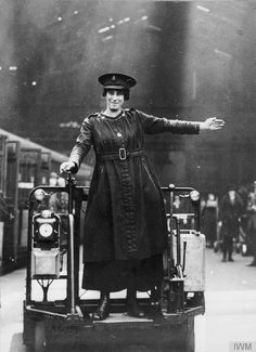 A female trolley driver signals a left turn on a platform at Liverpool Street Station, Great Eastern Railway - Photographer Horace Nicholls