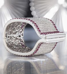 This stunning diamond and ruby cuff bracelet makes a bold statement. Laden with approximately 59.00 total carats of beautifully matched white diamonds, the extraordinary cuff is bordered by approximately 40.00 total carats of luxurious Burma rubies. Handcrafted and superbly finished, this chic bracelet is the epitome of glamour. Set in 18k white gold ~  Valentines Day Gifts for Her ~ M.S. Rau Antiques