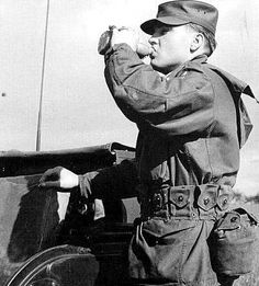 Elvis on maneuvers, November 1958 in Germany. Drinking water from a canteen.