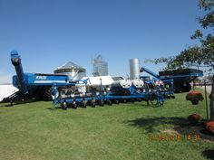 16 row Kinze 4900 corn planter with 1051 & 1100 grain carts serving as background