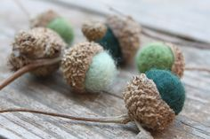 These 6 acorns were made by needle felting wool roving into acorn shapes and then wet felting it into shapes. I attached Swamp Oak acorn caps with hot glue. They all measure around 1 inch in size and have small branches still attached to them.    There are 2 forest green acorns, 2 moss green acorns, and 2 sage green acorns that are attached to the same branch. These are a beautiful bit of nature for the home.  $12