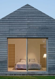 Horizontal wood plank siding covers this modern house, while sliding glass doors open the bedroom up to the outdoors.
