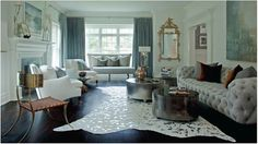 """This is exactly how to """"unstuff"""" an otherwise stuffy, traditional room - add a killer pair of coffee tables, and a metallic silver cowhide rug."""