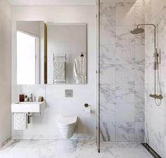 Piccolo ma elegante bagno che utilizza il marmo bianco su pavimento e zone d'acqua. Interessante idea per il taglio di luce che illumina la doccia