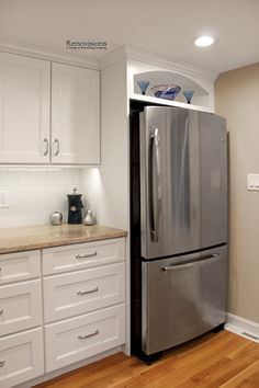 A recent kitchen remodel by Renovisions. White painted shaker style cabinetry, granite countertops, white subway tile backsplash, chrome handles, stainless steel appliances, stainless steel sink, hardwood floors, oak floors