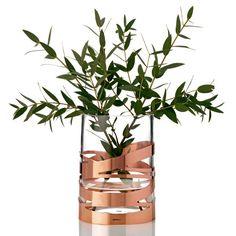 Nyd gløden med den nye flotte glasvase, Tangle fra Stelton. Vasen har et dekorativt kobberbånd, der smyger sig om glasset i en uforudselig indbyrdes orden. Uanset vinklen du ser vasen fra, er kobberbåndet dynamisk og giver vasen et foranderligt udtryk. Tangle tilføjer et element af luksus i dit hjem, da kobberbåndet, som smykker glasset, funkler af både kvalitet, stil og ynde.
