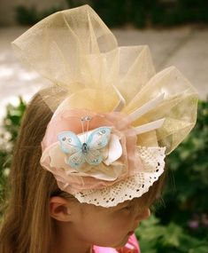 """DIY Tea hats.5"""" felt base on skinny metal headband. 2 colors of tulle. 2 butterflies on wires. 3 short pieces of ribbon .Doilley. Feathers Fabric roses."""
