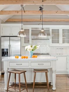 source: Terrat Elms Interior Design  Kitchen design with gray walls paint color, cathedral ceiling, exposed wood beams, white kitchen cabinets & kitchen island, glossy subway tiles backsplash, polished chrome pendants, marble counter tops and sawhorse stools.