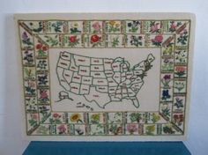 A beautiful cross stitched piece of Americana folk art with the map of the United States in the middle and the state flowers framing it. The piece is in amazing condition. It is stapled to a foam frame but could be removed and framed professionally.   Dimensions 24 inches wide and 18 inches tall