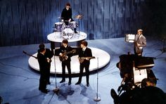 Sullivan chats with Beatles members Paul McCartney, George Harrison, John Lennon, and Ringo Starr on the set of his show in 1964.