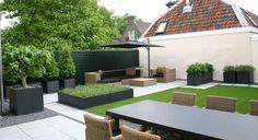 Rodenburg tuinen: modern dakterras in Utrecht met kunstgras en moderne betontegels. Een onderhoudsvriendelijke tuin met aluminium bloembakken. De moderne betontegels worden ingezet om terrassen met lounge set en eettafel te kunnen huisvesten.