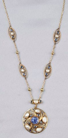 Arts & Crafts 18kt Gold, Sapphire, and Freshwater Pearl Necklace, Margaret Rogers, Boston, designed as a circular pendant bezel-set with a sapphire measuring approx. 10.00 x 8.90 mm, framed by circular-cut sapphires, shaped pearls, and wire scrolls, suspended from a chain of navette-form links each set with bezel-set sapphires and pearls, dia. 1 5/8, lg. 16 1/4 in., signed MR.