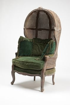 A Louis XV style carved wood and cane porter's chair. Early 20th century, the hooded, domed back surmounted by a floral crest and joined by padded scrolled arms to the serpentine padded seat, over a serpentine floral-carved apron raised on cabriole legs ending in scroll feet.