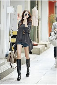 Cute fall outfit: leather boots, denim shorts, and a light, oversized sweater.